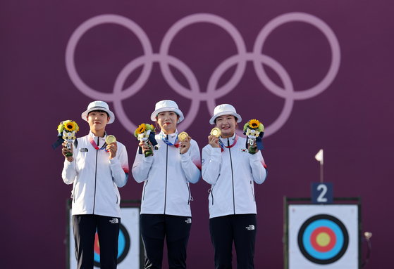 Archers An, Jang Min-hee and Kang Chae-young of the Korean women's archery team pose after winning a gold medal for women's team at the 2020 Tokyo Olympics on July 25. [JOINT PRESS CORPS]