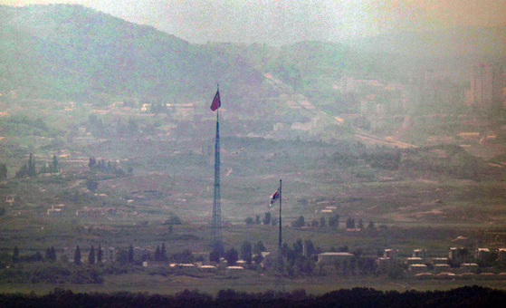 The flag of South Korea, right, and the flag of North Korea, left, stand close together in a border area between the two Koreas on July 27. [YONHAP]