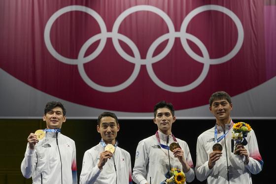 The Korean men's sabre team, from left, Gu Bon-gil, Kim Jung-hwan, Kim Jun-ho and Oh Sang-uk celebrate on the podium at the 2020 Summer Olympics on July 28 in Chiba, Japan. [AP/YONHAP]