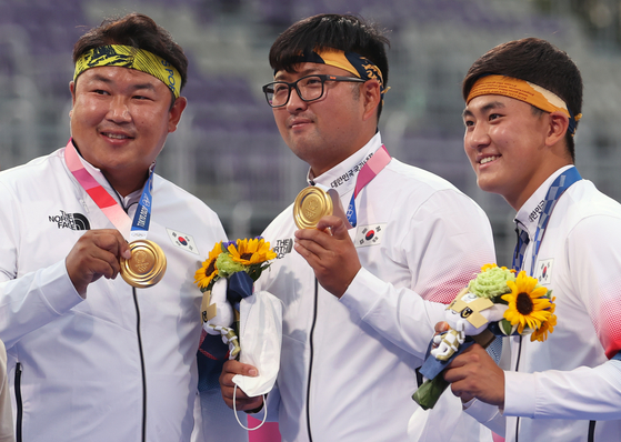 From left, Oh Jin-hyek, Kim Woo-jin and Kim Je-deok hold up their archery men's team gold medals on the podium on July 26 at Yumenoshima Park Archery Field in Tokyo. [YONHAP]