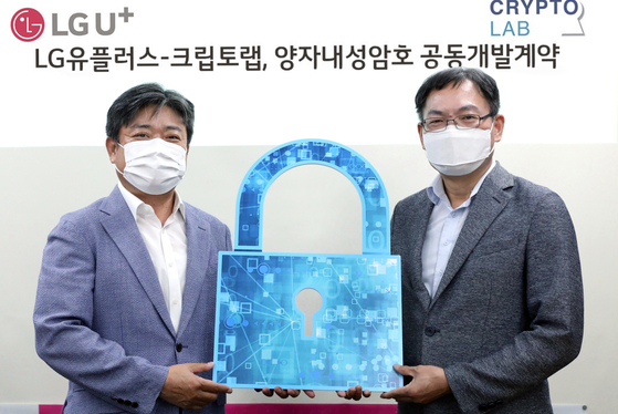 LG U+ Vice President Choi Taek-jin, left, stands with Cheon Jung-hee, founder and CEO of cryptographic company CryptoLab, holding a lock-shaped prop after signing an investment deal on Sunday. LG U+ will invest in CryptoLab to build a 5G and 6G network safe from quantum computer attacks, the telecom company said. [LG U+]