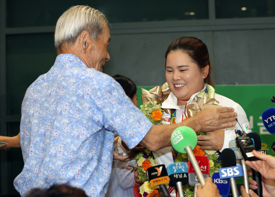 Park In-bee's grandfather congratulates her after she won gold at the 2016 Rio Olympics, welcoming her at Incheon International Airport on Aug. 23, 2016. [ILGAN SPORTS]