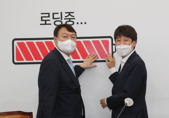 Lee Jun-seok, right, chairman of the main opposition People Power Party (PPP), poses next to the image of a full-charged battery, symbolizing all presidential contenders joining the race, along with Yoon Seok-youl, left, former prosecutor general and presidential front runner, after Lee had a meeting with Yoon in the National Assembly on Monday. Yoon announced he will join the PPP on Friday while Lee was out of Seoul. [YONHAP]