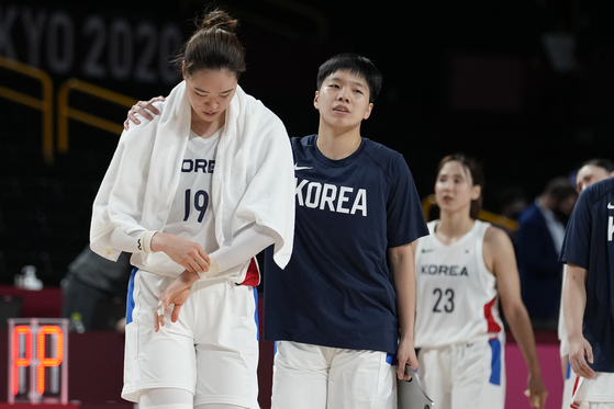 The Korean national basketball team players walk off the court after losing to Serbia 65-61 during a women's preliminary round basketball game at the 2020 Summer Olympics on Sunday in Saitama, Japan. [AP/YONHAP]