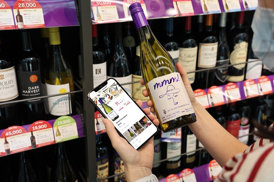 A customer holds a wine bottle to look for information on the soon-to-launch wine curation service on convenience store CU's mobile app Pocket CU. [BGF RETAIL]