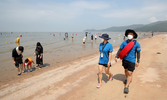 Lifeguards patrol Hanagae Beach in Incheon on Tuesday to make sure visitors wear masks to prevent infections of Covid-19. Abiding by Level 4 social distancing measures, the Incheon Metropolitan Government temporarily closed all beaches in the region, allowing visitors but prohibiting merchants and the setting up of parasols. [YONHAP]