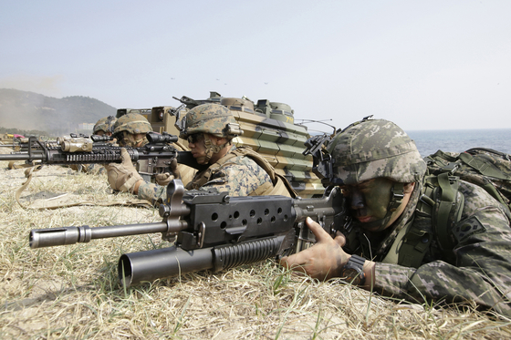In this March 30, 2015, file photo, marines of Korea, right, and the U.S aim their weapons near amphibious assault vehicles during Korea-U.S. joint landing military exercises as part of the annual joint military exercise Foal Eagle between the two countries in Pohang. Since 2018, the two countries stopped holding joint field exercises and replaced them with computer simulation drills from command posts.  [AP]