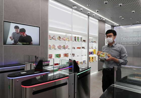 A model tries out an automatic payment system at a 7-Eleven convenience store in Geumcheon District, southern Seoul, on Tuesday. At the store, which the company calls a digital transformation store, a total of 26 high performance cameras are set up to analyze which products customers pick up from which shelf. Various systems are tested at this store before they are applied to other convenience stores. [YONHAP]