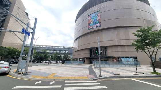 The street outside Busan's Shinsegae Centum City Mall stands empty on Tuesday after an employee tested positive on Monday. The store where the employee worked temporarily closed on Tuesday. The mall is connected to Shinsegae Department Store, where 11 cases were reported after a worker at its Chanel store tested positive on July 28. [YONHAP]