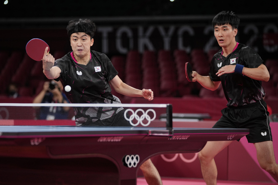 Korea's Jeong Young-sik, left, and Lee Sang-su compete during the table tennis men's team semifinal match against China's Xu Xin and Ma Long at the 2020 Tokyo Olympics in Tokyo on Wednesday. [AP/YONHAP]