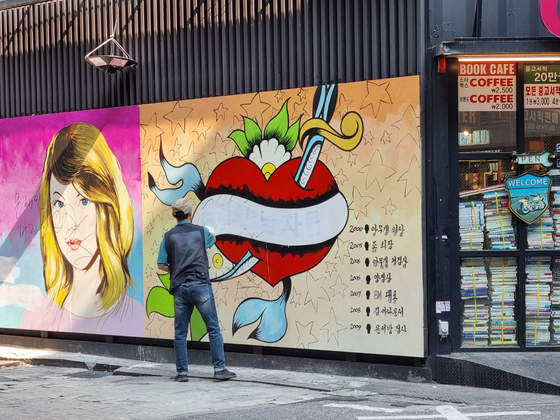 A provocative mural on the wall of a bookstore in central Seoul, aimed at disgracing the wife of former Prosecutor General Yoon Seok-youl, frontrunner among presidential candidates, is being erased by an employee of the bookstore. [JO HAE-UN]