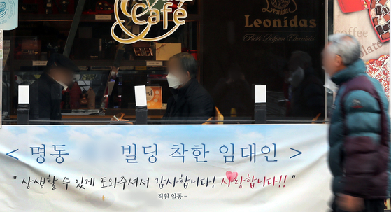 A passerby walks by a banner in Myeong-dong, central Seoul, thanking the landlord for lowering rents during the coronavirus pandemic on Feb. 24. [NEWS1]
