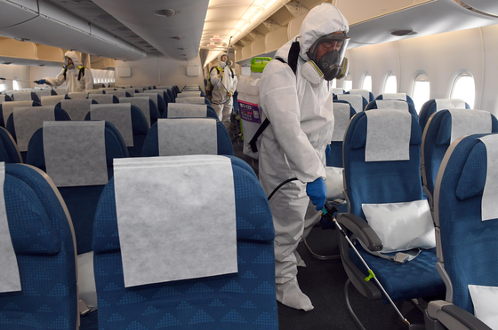 Quarantine inspectors sterilize a plane parked at the Incheon International Airport in March 2020. [JOONGANG PHOTO]