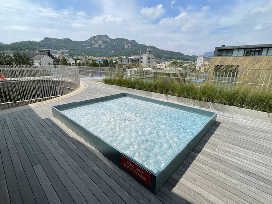 The outdoor terrace connected to the exhibition room features a photo of a pool in a frame [LEE SUN-MIN]