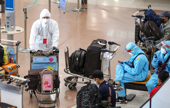 Migrant workers from Indonesia, wearing full protective gear, enter the arrival gate at Incheon International Airport on Thursday in spite of the exponentially spreading Covid-19 Delta variants. [YONHAP]