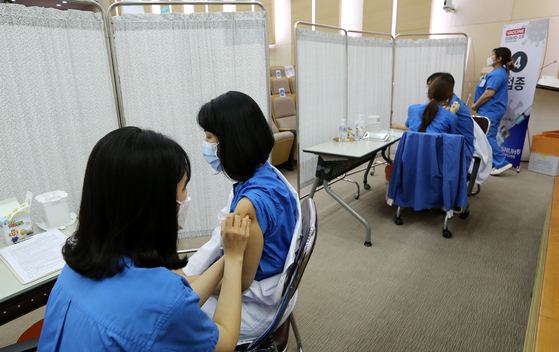In this file photo, doctors, nurses and nursing assistants of the Seoul National University Hospital receive AstraZeneca shots on March 5, 2021. The hospital vaccinated its 8,300 workers in March.  [NEWS1]