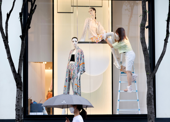 A staffer at a clothes store in Myeong-dong, central Seoul, changes a mannequin into autumn-wear on Aug. 8, a day after Ipchu, or the official start of autumn according to Korea's traditional calendar. [YONHAP]
