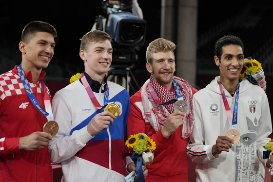 Medalist Croatia's Toni Kanaet, left, Maksim Khramtsov of the Russian Olympic Committee, second from left, Jordan's Julyana Al-Sadeq , second from right, and Egypt's Seif Eissa hold medals as they pose for photographers after a ceremony for taekwondo men's 80kg at the 2020 Summer Olympics on July 26. [REUTERS/YONHAP]