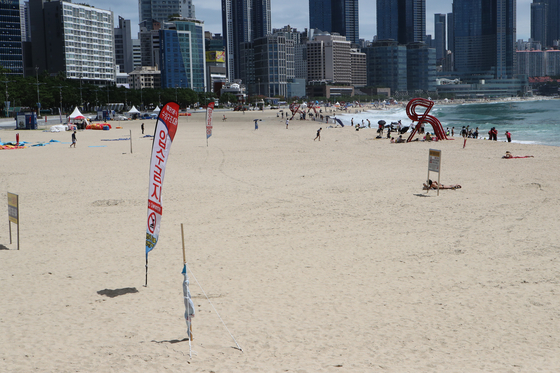 Visitors are sparsely seen at Haeundae Beach in Busan on Monday. Busan Metropolitan Government decided to close down operations of seven beaches, including Haeundae, from Tuesday as the social distancing level was upgraded to Level 4 in the city. [SONG BONG-GEUN]