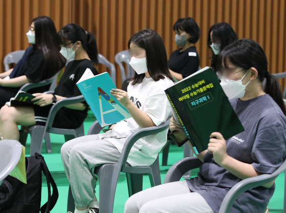 Highschool seniors read workbooks while waiting to receive Covid-19 vaccine shots at a vaccination center in Daejeon on Monday, 101 days before the country's College Scholastic Ability Test (CSAT) in November. [NEWS1]