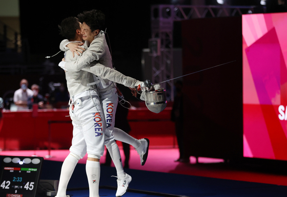 Korean sabrist Oh Sang-uk, left and Gu Bon-gil celebrate the men's sabre team's win against Germany in the semifinals on Wednesday at the Makuhari Messe Hall in Chiba, Japan. [YONHAP]