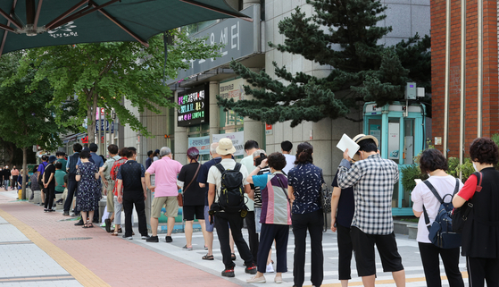 People wait in line to apply for unemployment allowances at an employment center in Nowon District, northern Seoul, on Monday. The Covid-19 pandemic has led to the loss of many jobs. [YONHAP]