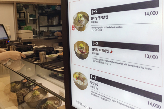 A menu shows naengmyeon, noodles in cold meat broth, priced at 13,000 won ($11) and 14,000 won at a store in Myeongdong, central Seoul, on Monday. According to the Korea Consumer Agency, naengmyeon was priced at an average 9,577 won at restaurants in July, up 6.41 percent on year. [YONHAP]