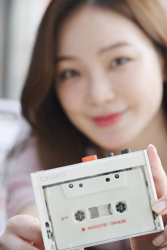 A model holds KT's Kassette. The Kassette will be sold starting Tuesday as part of KT's project Kassette X Rewind, through which singers such as Baekhyun of Exo, Doyoung of NCT and IZ*ONE have released tracks on cassette. [YONHAP]