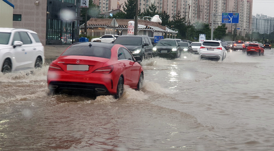 Cars drive through a flooded road in Gangneung, Gangwon, after heavy rainfall in Korea's east coast Sunday due to the indirect influence of tropical storm Lupit. [YONHAP]