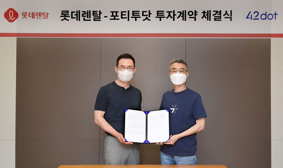Lotte Rental CEO Kim Hyun-soo, left, and 42dot CEO Song Chang-hyun pose for a photo after signing an investment deal on Monday. [LOTTE RENTAL]