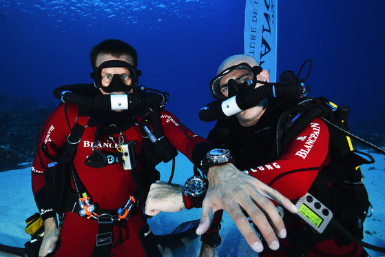 Marc A. Hayek, right, president and CEO of Switzerland-based luxury watch brand Blancpain, poses for a photo with the Fifty Fathoms watch during an ocean expedition. [BLANCPAIN]