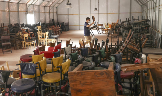 A secondhand store employee stacks chairs once used at restaurants that recently shut down due to Covid-19 at a warehouse in Ansan, Gyeonggi, on Tuesday. According to the Ministry of Employment and Labor, 647,000 food businesses were subscribed to the employment insurance program as of July, down 2.3 percent on year, meaning a decrease in operating businesses. [YONHAP]