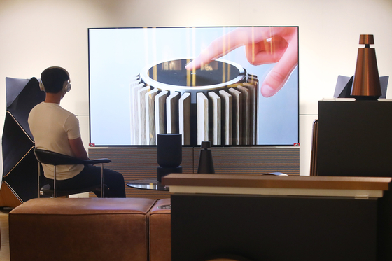 A model tests Bang & Olufsen's speaker, TV and headphones at the company's store in Gangnam District, southern Seoul. With more people staying home due to Covid-19, home theater products are gaining popularity. [YONHAP]
