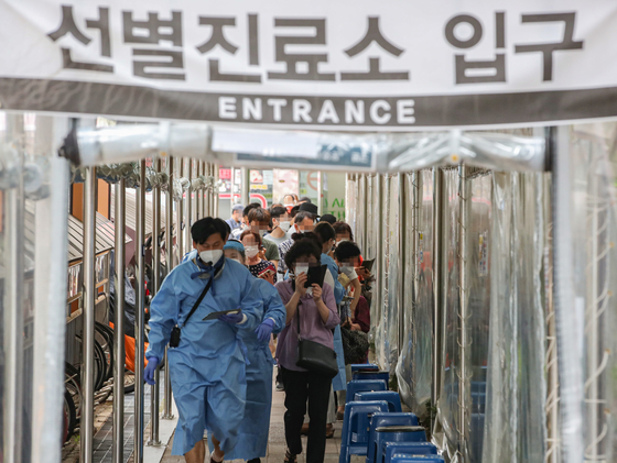 People wait in a long line to get tested for Covid-19 at a testing center in Gwanak District, southern Seoul, on Wednesday morning, when the country's daily new infections surged to a record 2,223. [YONHAP]