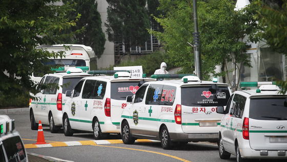 Ambulances transport Covid-19 patients to a dormitory-turned treatment facility for mild cases in Kyonggi University in Suwon, Gyeonggi, on Wednesday. Korea's daily Covid-19 infections hit a record 2,223 on Wednesday. [YONHAP]