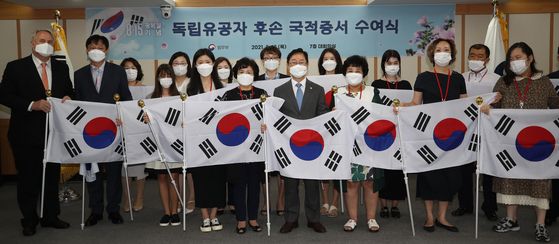 Descendants of independence fighters against imperial Japan pose holding the Korean national flag with Justice Minister Park Beom-kye, center, at the Justice Ministry in the central government complex in Gwacheon, Gyeonggi, on Thursday, after they received the certificate of Korean nationality. [YONHAP]