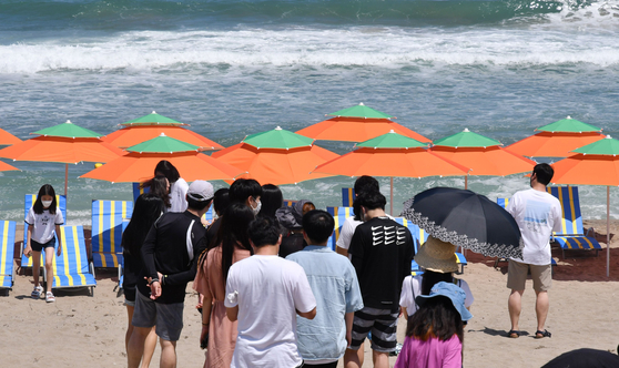 """Visitors to Maengbang Beach in Samcheok are waiting in line to recreate the concept photos of BTS's """"Butter."""" [SAMCHEOK CITY GOVERNMENT]"""