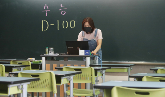 A teacher instructs her high school senior students online in an empty classroom at Suwon High School in Suwon, Gyeonggi, on Tuesday, 100 days before the College Scholastic Ability Test (CSAT). The students are taking online classes at home because of the Covid-19 pandemic. [YONHAP]