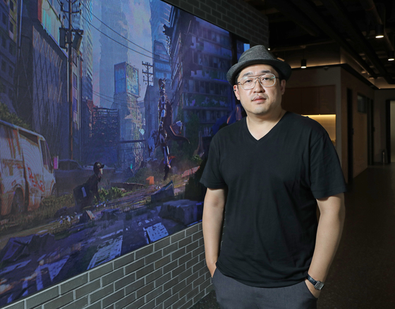 Park Jeong-seo, the CEO of Kakao Webtoon Studio, poses for photos after an interview with the Korea JoongAng Daily at the company's office in Pangyo, Gyeonggi, on Aug. 11. Behind Park is an introductory video of Kakao Webtoon's new launch playing on a screen. [PARK SANG-MOON]