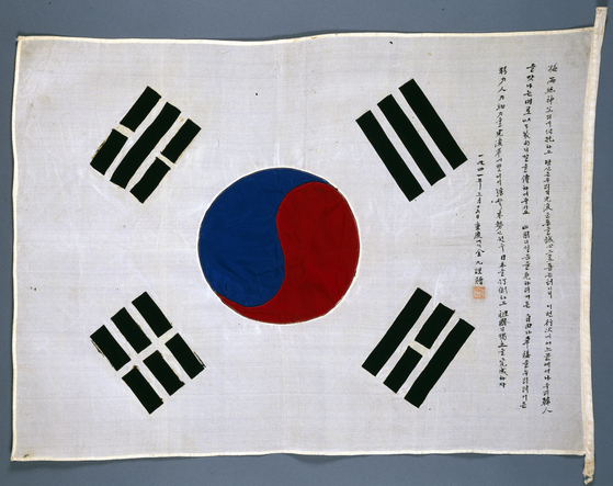 A Taegeukgi signed by freedom fighter Kim Gu (1876-1949) has Kim's handwritten text on the right of the flag describing his desire for Korean independence. [CULTURAL HERITAGE ADMINISTRATION]