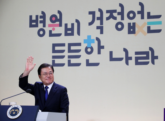 President Moon Jae-in waves his hand at participants in the virtual event to commemorate the fourth year since the introduction of Mooncare, a policy of lowering medical costs for the general public, at the Blue House on Thursday. [JOINT PRESS CORPS]