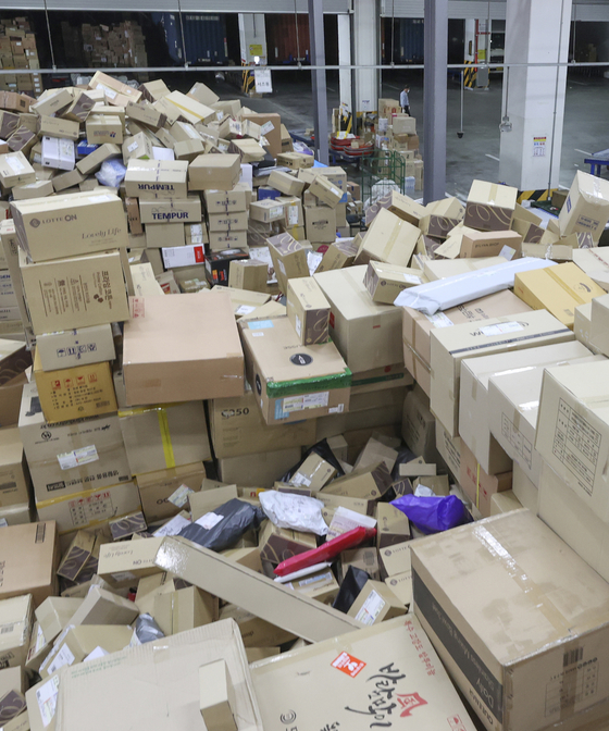 Packages waiting for delivery pile up at a logistics center in Seoul on Sunday as delivery workers take a mandatory three-day break from their work. Logistics companies designated every 14th as a day off for employees in order to ensure workers' health. This month, the break last for three days as the substitutive holiday for Liberation Day was designated on Monday. [YONHAP]
