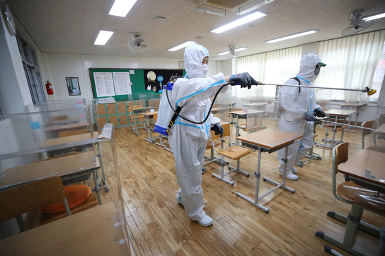 Sanitization workers disinfect a high school classroom in Daegu on Sunday afternoon ahead of the school reopening. [YONHAP]