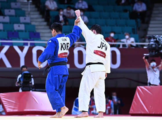 Korean judoka Cho Gu-ham, left, lifts his Japanese opponent's hand after losing to him in the final match of the men's 100-kilogram weight class in the Tokyo Olympics. [JOINT PRESS CORPS]