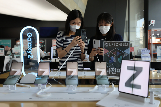 Employees try out Samsung Electronics' Galaxy Z Fold 3 and Galaxy Z Flip 3 at the KT Square in Jongno District, central Seoul, on Tuesday. Preorders for the two smartphones, Galaxy Watch 4 and Galaxy Buds 2 wireless earphones are taken from Tuesday to Aug. 23. Preorder customers will be given complimentary gifts and after-care discounts, and they will start receiving their orders on Aug. 24. Official sales start Aug. 27. [YONHAP]
