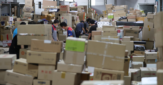 Delivery workers sort packages at a logistics center in Seoul on Tuesday as parcel deliveries resume. Parcels hadn't been delivered since Aug. 14, an extra holiday granted to delivery workers, followed by National Liberation Day and a substitute holiday on Monday, giving the workers a three-day break. [YONHAP]