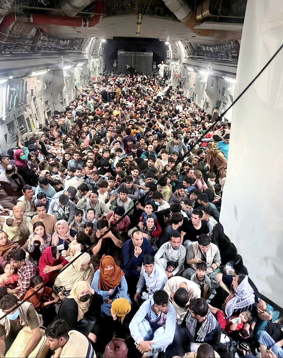 Evacuees are seen inside a U.S. Air Force C-17 Globemaster III transport aircraft, which carried some 640 Afghans to Qatar from Kabul, Afghanistan on Aug.15. [REUTERS/YONHAP]