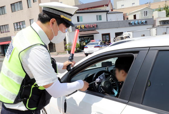A police officer gives a random breathalyzer test to a driver in Jeju on Wednesday in an effort to curb daytime drunken driving as daytime drinking has been increasing under Level 4 social distancing measures. [NEWS1]