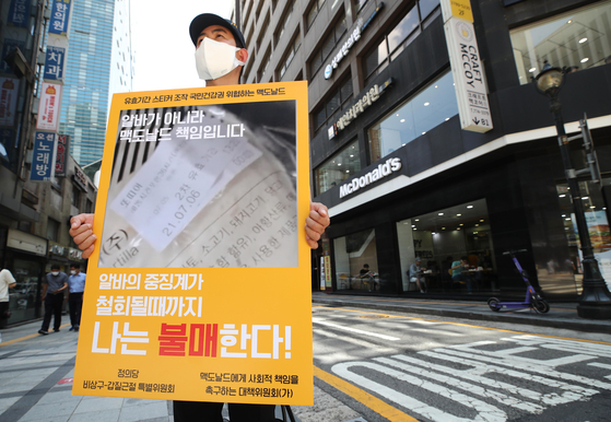 Park Chang-jin, vice chairman of the Justice Party, holds a one-man protest on Aug. 9 outside a McDonald's in Jung District, central Seoul, urging a boycott of the company. [YONHAP]