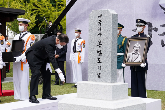 President Moon Jae-in sprinkles soil from Kazakhstan over the casket containing the repatriated remains of Korean independence fighter Hong Beom-do during his burial ceremony Wednesday at the Daejeon National Cemetery. [NEWS1]